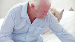 Old man suffering from a headache and taking medicine. In his bedroom stock video footage