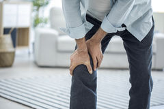 Old man suffering from knee pain. Old man standing suffering from knee pain Royalty Free Stock Photos