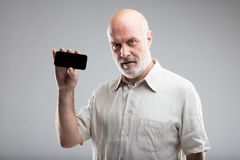 Old man suggesting a smartphone online app. Old man holding a smartphone suggesting you to use some useful apps Royalty Free Stock Photos