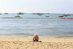 Old man sunbathe at the beach, Pattaya Thailand, as background. Or print card Stock Photography