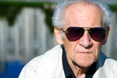 Old Man in Sunglasses. Closeup portrait of an old serious man in sunglasses Royalty Free Stock Photography