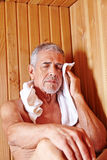 Old man sweating in sauna. Old man with towel sweating in sauna of spa hotel Stock Photo