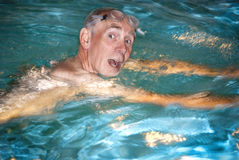Old man swimming in pool Royalty Free Stock Photography