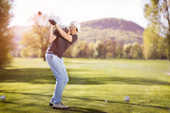 Old man swinging golf club. Royalty Free Stock Images