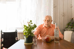Old Man at the Table with Wine, Apple and Plant Royalty Free Stock Photos