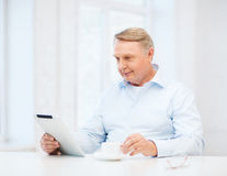 Old man with tablet pc computer at home Royalty Free Stock Photography