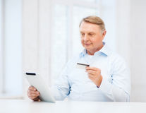 Old man with tablet pc and credit card at home Stock Photography