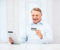 Old man with tablet pc and credit card at home Royalty Free Stock Photo
