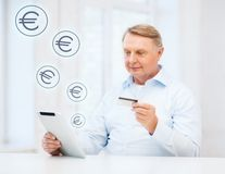 Old man with tablet pc and credit card at home. Business, oldness, online banking, internet shopping and oldness concept - smiling old man with tablet pc and Stock Image
