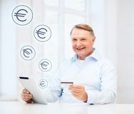 Old man with tablet pc and credit card at home Royalty Free Stock Image