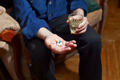 Old Man Taking Medicine. Old man sitting in a chair and holding pills and glass of water in his hands, he is going to take some medicine Royalty Free Stock Photos