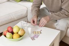 Old man taking medicines Stock Photography