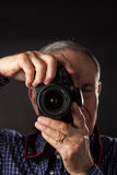 Old man taking a picture. On dark background Royalty Free Stock Photos
