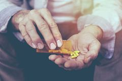 Old man taking a pill stock images
