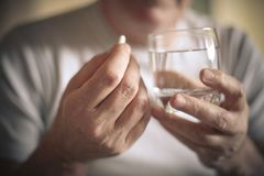 Old man taking a pill. royalty free stock photography