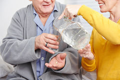 Old man taking pill with water Royalty Free Stock Photography