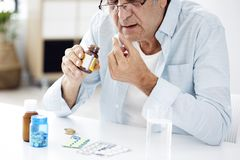 Old man taking pills. In home stock images