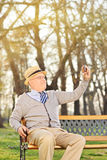 An old man taking a selfie seated on bench outdoors Royalty Free Stock Photo