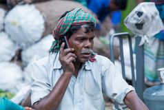 A old man while talking on her mobile phone at market royalty free stock photo