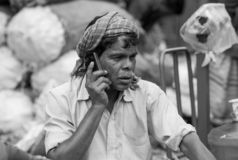 A old man while talking on her mobile phone at market stock photo