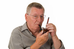 Old man tamping pipe. Old man tamping a pipe - isolated Royalty Free Stock Photo