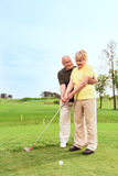 Old man teaching his wife to play golf. Teaching with love. Old men standing on course behind his wife and teaching her to play golf Royalty Free Stock Photography