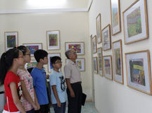 Old man and teens watch picture exhibition Royalty Free Stock Images