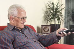 Old man with television remote control Stock Photos