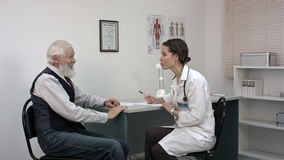 Old man telling the female doctor about the pain in the neck. stock video