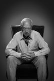 Old man thinking and waiting. Old man sitting on the armchair, looking with power glance Royalty Free Stock Images