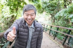 Old man thumb up. Old man smile happily and thumb up in the park royalty free stock photo