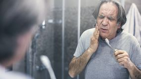 Old man with toothache in front of mirror stock photography