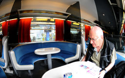Old man in train. Bald old man in glasses reading newspaper on the train Royalty Free Stock Photography