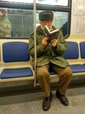 Old man in two glasses reading a book sitting in a train.