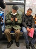 Old man in two glasses reading a book sitting in a train. Stock Photo