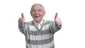 Old man with two thumbs up. Happy senior man giving two thumbs up, isolated on white background. Human facial expressions and body langauge stock video footage