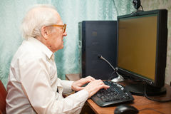 Old Man Typing. Portrait of a senior man typing something on his computer Stock Photos