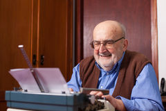 Old man typing on a typewriter Stock Photos