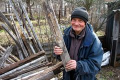 An old man in untidy clothes chooses from a pile of old wood boards to heat the house, loneliness in the village stock photography