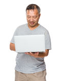 Old man use of laptop computer Stock Photography