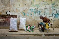 Old man uses a brick to smash aluminum cans for cash. HAVANA, CUBA JUNE 19, 2016 An old man, sitting on a chair, smashes aluminum cans with a brick, to sell and Royalty Free Stock Image