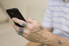 Old man using a black smartphone at home, texting. Old man with tattooed hands using a black smartphone, close-up Stock Images