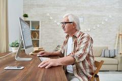 Old man Using Computer at Home Royalty Free Stock Photo
