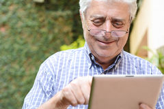 Old man using digital tablet. Royalty Free Stock Images