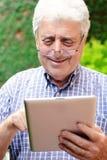 Old man using digital tablet. Stock Photos