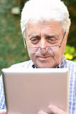 Old man using digital tablet. Royalty Free Stock Photo