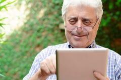 Old man using digital tablet. Stock Photo