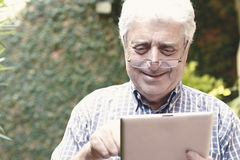 Old man using digital tablet. Stock Images