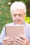 Old man using digital tablet. Stock Photography