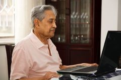 Old man using internet. Elderly Indian man using a laptop computer at home Stock Photography
